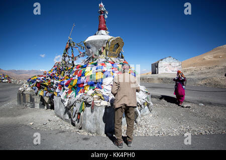 Local people in traditional clothes praying at Tanglangla Pass in the Himalayas along the Leh-Manali Highway, Ladakh, - Stock Photo