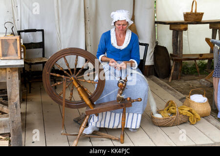 Close up of a woman making yarn from wool on a foot operated spinning wheel on the Mount Vernon estate, Virginia, - Stock Photo