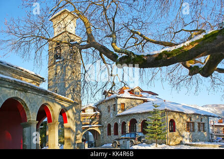 The tall bell tower with clock of the stone Church of Agia Paraskevi in center of Metsovo, Greece. - Stock Photo