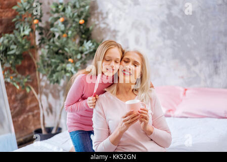 Family members. Positive delighted nice girl hugging her grandmother and closing her eyes while enjoying their time - Stock Photo