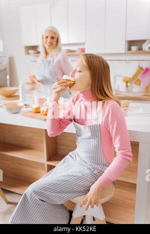 Very tasty. Positive nice pretty girl sitting on a stool and eating a bun while enjoying her food - Stock Photo