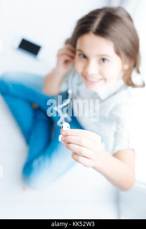 Unbelievable emotions. Selective focus of an earpiece stretched by sitting little exuberant girl who smiling at - Stock Photo