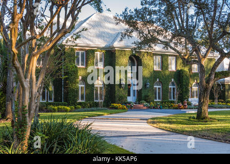 Ivy covered home in the dappled light of sunset at Sawgrass Players Club, a gated golf community in Ponte Vedra - Stock Photo