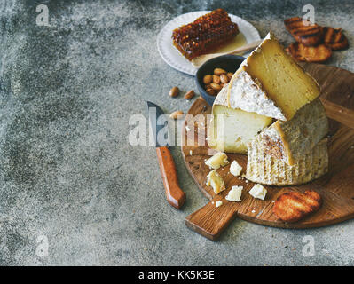 Cheese assortment and snacks on rustic wooden board, copy space - Stock Photo