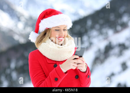 Portrait of a happy girl sending christmas messages on a smart phone on holidays with a snowy mountain in the background - Stock Photo