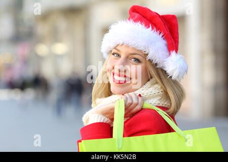 Portrait of a happy girl wearing santa claus hat shopping in christmas looking at you outdoors on the street - Stock Photo