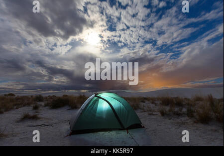 Tent in moonlight in White Sands Dunes, New Mexico,USA - Stock Photo