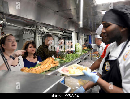 171123-N-MJ491-138 SAN DIEGO (Nov. 23, 2017) Sailors, friends and family members are served food during Thanksgiving - Stock Photo