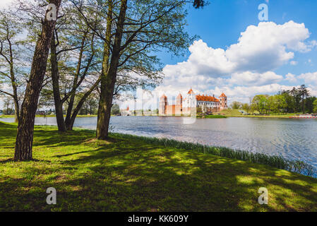 Medieval Mir Castle Complex in Belarus. Ancient brick Mirsky castle and clouds reflected on blue water. Unesco world - Stock Photo