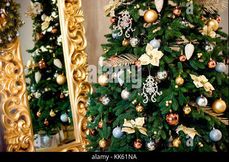 Beautiful decorated Christmas tree with red and goldish baubles and garland, in the new-year background with fireplace - Stock Photo