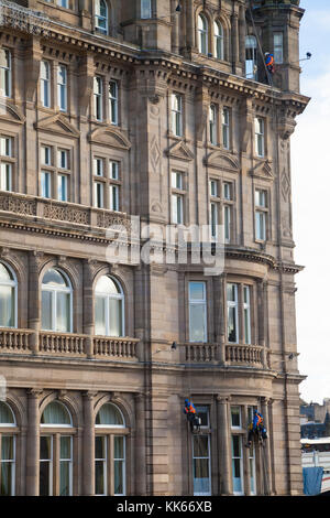 Window cleaners abseiling on the Balmoral Hotel to clean windows. - Stock Photo