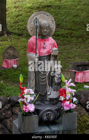 Nara - Japan, May 30, 2017: Traditional stone carved Jizo with red skirt honored and respected with flowers - Stock Photo