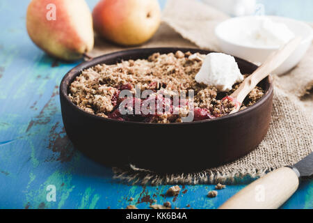 Pear and berry crumbles served with cream in rustic ceramic bowl - Stock Photo