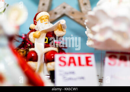 Ceramic or Bone China Santa Claus figure reading the naughty or nice list on sale in a display in a shop window - Stock Photo