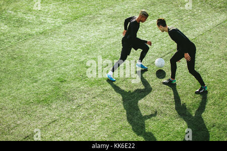 Top view of two teenagers playing football during team practice in field. Young soccer players playing on the sports - Stock Photo