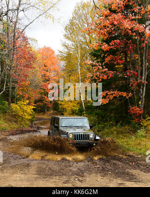 Jeep Rubicon Wrangler splashing through a water and mud puddle in the Adirondack NY forest. - Stock Photo