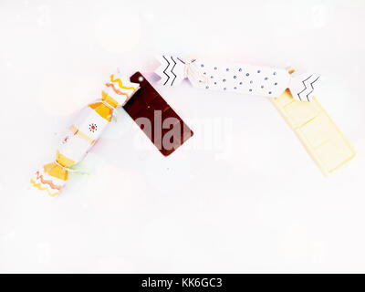 Christmas Decoration with cracker chocolate box and dark and white chocolate bar with colorful bokeh for holidays - Stock Photo