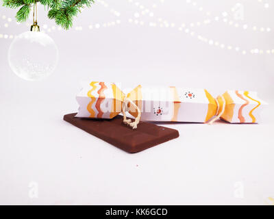 Christmas Decoration with cracker chocolate box and dark chocolate bar with christmas ball for holidays best background - Stock Photo