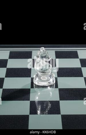 glass knight standing on chess board - Stock Photo