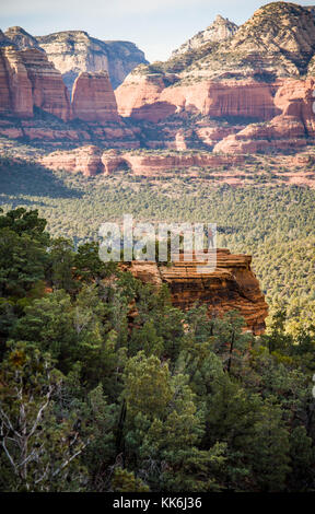A lone woman hiker atop a rocky outcrop overlooking the red rock canyons outside Sedona, Arizona, USA. - Stock Photo