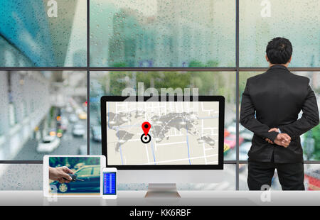 Back side of Businessman looking at traffic jam with Rain drop On the window Glass with technology Computer set - Stock Photo