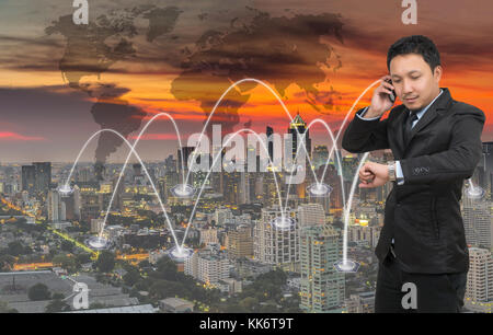 Asian businessman calling mobile phone with network connection on cityscape with world map background, Business - Stock Photo