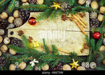 old cutting board with christmas attributes on a wooden kitchen background - Stock Photo