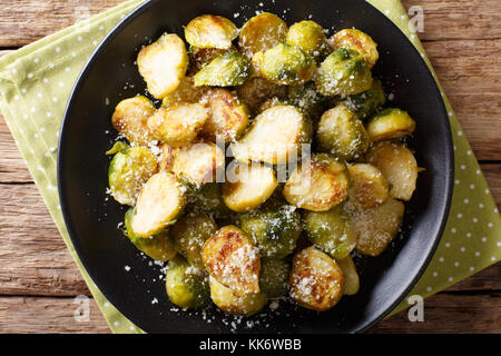 Healthy food: roast Brussels sprouts with a Parmesan cheese close-up on a plate on a table. Horizontal top view - Stock Photo