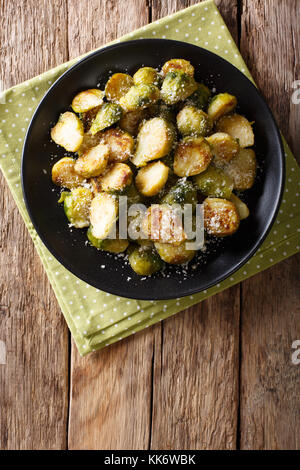 Vegetarian food: fried Brussels sprouts with garlic and Parmesan cheese close-up on a plate on a table. Vertical - Stock Photo