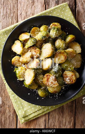 roasted brussels sprouts with garlic and Parmesan cheese on a plate close-up on the table. Vertical top view from - Stock Photo