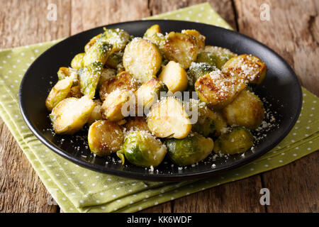 Vegetarian food: fried Brussels sprouts with garlic and Parmesan cheese close-up on a plate on a table. horizontal - Stock Photo
