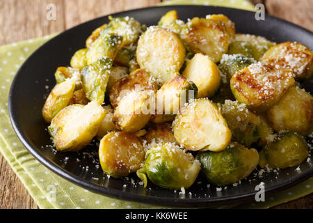 Delicious homemade fried brussels sprouts with Parmesan close-up on a plate on the table. horizontal - Stock Photo