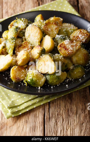 Healthy food: roast Brussels sprouts with a Parmesan cheese close-up on a plate on a table. vertical - Stock Photo