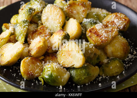 fried Brussels sprouts with Parmesan cheese close-up on a plate on a table. horizontal, rustic - Stock Photo