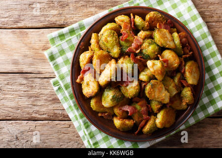 fried in breaded Brussels sprouts with bacon close-up on a plate on a table. horizontal top view from abovel, rustic - Stock Photo