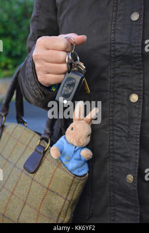 working mother, car keys in hand, with a child's toy rabbit sticking out of her bag - Stock Photo