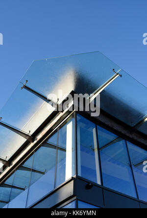 Glass canopy suspended on stainless steel brackets above glass curtain wall on new development at the rock bury - Stock Photo