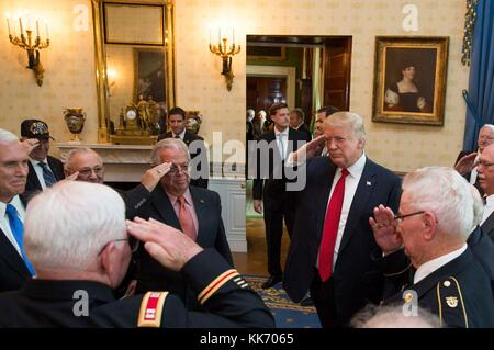 """U.S. President Donald Trump salutes Medal of Honor recipient retired U.S. Army Capt. Gary M. Rose, and fellow Vietnam veteran """"Battle Buddies"""", in the Blue Room of the White House October 23, 2017 in Washington, DC."""