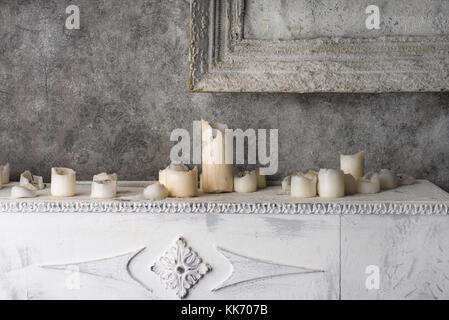 Burned wax candles on the old fireplace - Stock Photo