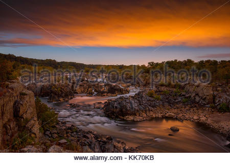 A fiery sunset colors the sky over the Great Falls of the Potomac River, located in Great Falls Park, Virginia. - Stock Photo