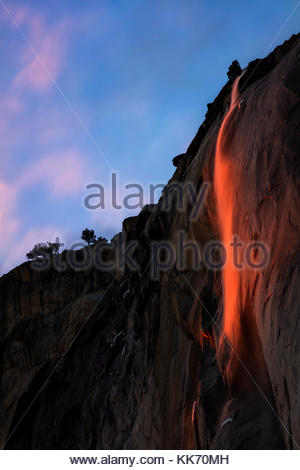 Horsetail Fall, a 1,000-foot (305-meter) waterfall, appears like lava at sunset as it pours over the granite face - Stock Photo