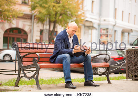 Man sitting on bench and reading his note paper. - Stock Photo