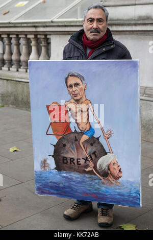 London, UK. 22nd November, 2017. Satirical artist Kaya Mar stands outside Downing Street with an artwork of Philip - Stock Photo