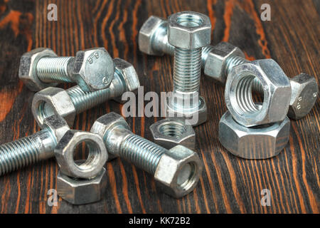 Bolts and nuts on a wooden surface. Close-up. Studio lighting. - Stock Photo