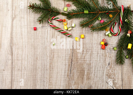 Christmas composition of fir branches, caramel sweets and caramel cane. On a light wooden background. - Stock Photo