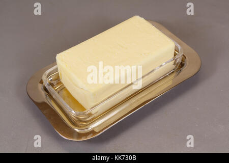 Pack of butter in a butter dish made of metal and glass - Stock Photo