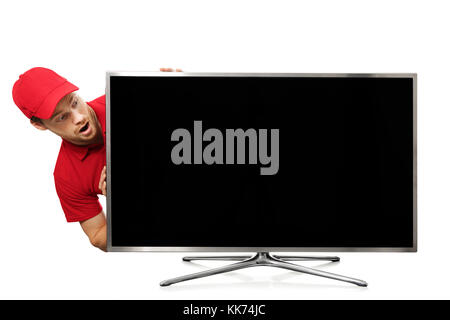 surprised young man in red uniform looking at big blank tv screen - Stock Photo