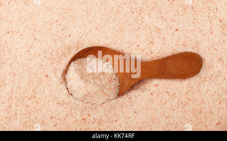 Close up one wooden scoop spoon in pink Himalayan salt, high angle view - Stock Photo