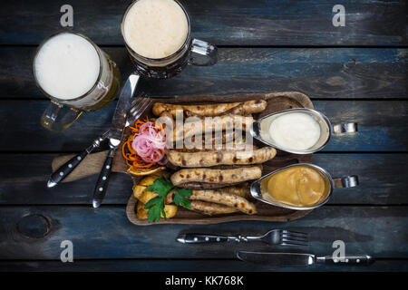 Grilled sausages with a mug of beer with potatoes sauce and cutlery on a wooden board. - Stock Photo