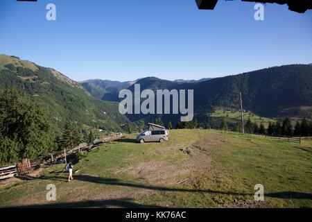 A female camper returning to her motorhome in a field high on a hill above the Rugova Valley Kosovo on a bright - Stock Photo